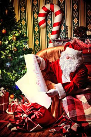 pere noel: Père Noël avec une liste de cadeaux de Noël assis dans un fauteuil confortable près de la cheminée à la maison.
