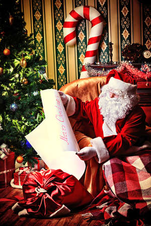 Santa Claus with a list of Christmas presents sitting in a comfortable chair near the fireplace at home.  photo