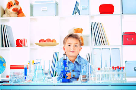 health education: Cute boy is making science experiments in a laboratory. Education. Stock Photo