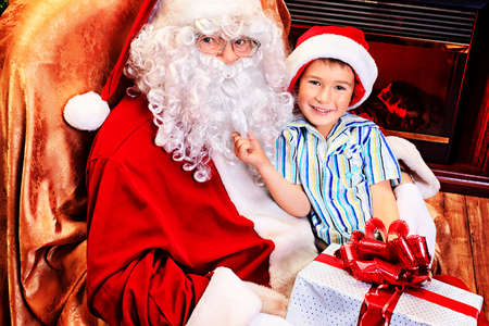 Santa Claus giving a present to a little cute boy near the fireplace and Christmas tree at home. Stock Photo - 16551737