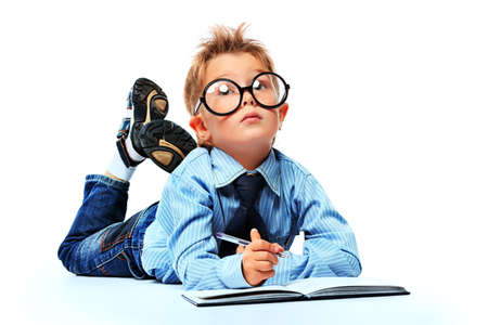 Little boy in spectacles and suit lying on a floor with a diary. Isolated over white background. photo