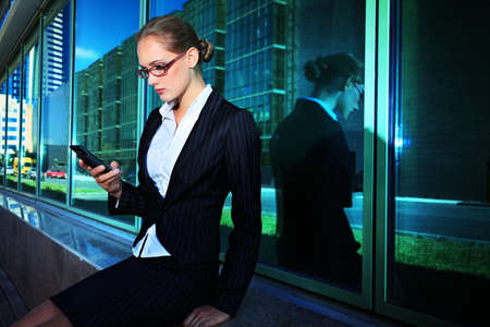 mobile phone adult: Young business woman talking on her mobile phone in the big city. Stock Photo