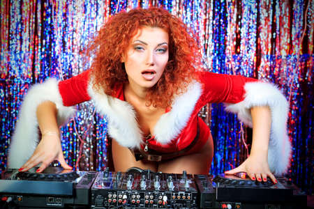 Attractive DJ girl mixing up some Christmas cheer. Disco lights in the background. Stock Photo - 16619289