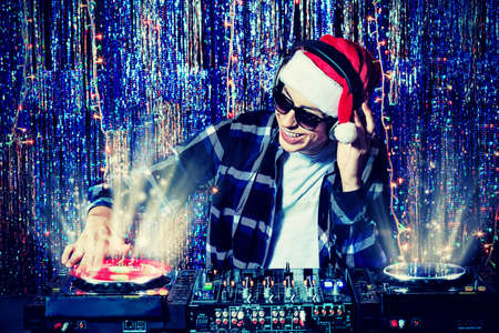 DJ man mixing up some Christmas cheer. Disco lights in the background.  Stock Photo - 16619294