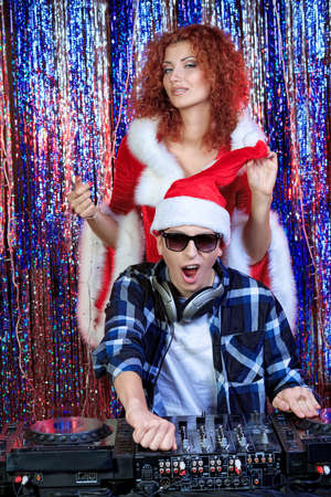 DJ man mixing up some Christmas cheer with attractive Snow Maiden. Disco lights in the background.  photo