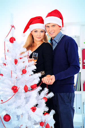 Happy young couple celebrating Christmas near the Christmas tree at home. Stock Photo - 16586532