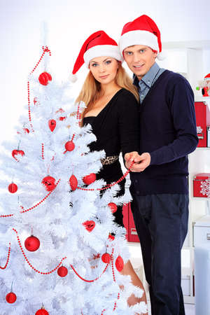 Happy young couple celebrating Christmas near the Christmas tree at home. Stock Photo - 16586530