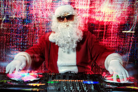disco lights: DJ Santa Claus mixing up some Christmas cheer. Disco lights in the background.