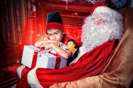 Santa Claus sitting with a little cute boy elf near the fireplace at home. photo