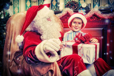 Santa Claus giving a present to a little cute boy near the fireplace and Christmas tree at home. Stock Photo - 16742328