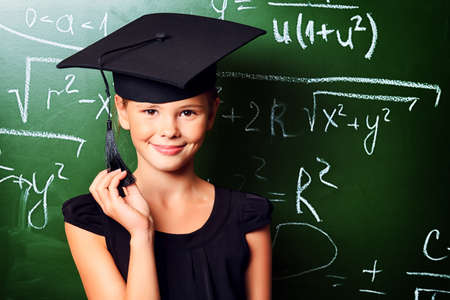 Portrait of a cute schoolgirl in academic hat and big round spectacles at a classroom. photo