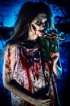 Pretty woman zombie standing at the night cemetery and tenderly holding a flower.  photo