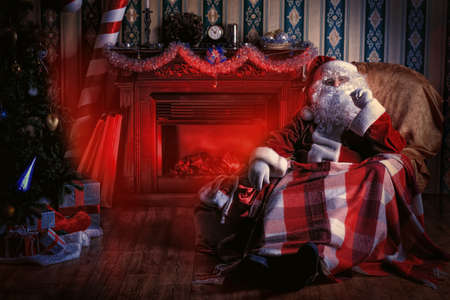 comfortable chair: Santa Claus with gifts sitting in a comfortable chair near the fireplace at home.