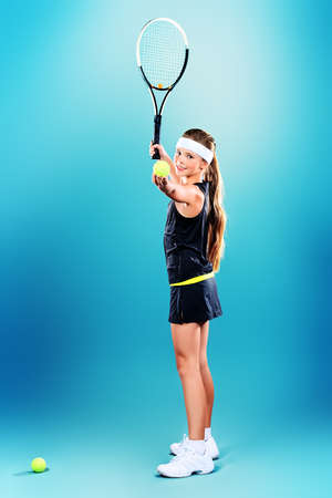 Portrait of a girl tennis player holding tennis racket and tennis ball. Studio shot.  photo