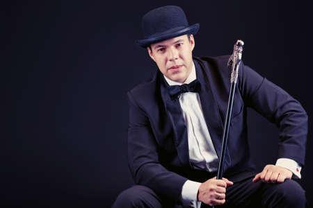 Portrait of an elegant man in black suit and black pot hat holding walking stick. Black background. Stock Photo - 16641281