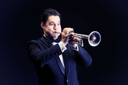 Portrait of a musician playing the trumpet. Black background. Stock Photo - 16641288
