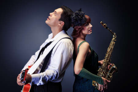 Couple of professional musicians in retro style posing in costumes at studio. Stock Photo - 16641267