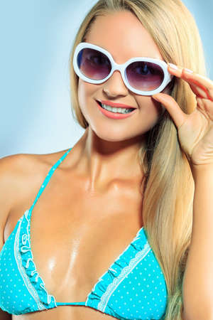 Portrait of a smiling young woman in bikini and sunglasses. Studio shot. Stock Photo - 16663292
