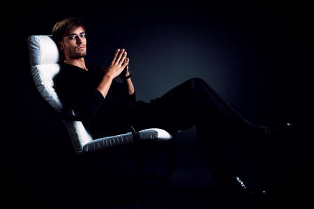 Portrait of a handsome man sitting in the armchair over black background. photo