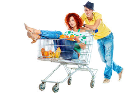 Cheerful couple with a shopping trolley. Isolated over white background. Stock Photo - 16671876