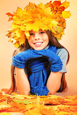 Portrait of a smiling girl in autumn clothes and a hat of maple leaves. Stock Photo - 16711682