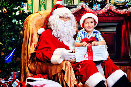 Santa Claus giving a present to a little cute boy at home. Stock Photo - 16711681