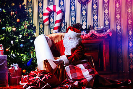 Santa Claus with a list of Christmas presents sitting in a comfortable chair near the fireplace at home. Stock Photo - 16711705