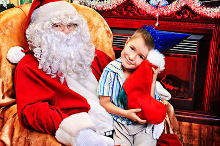 Santa Claus giving a present to a little cute boy at home. Stock Photo - 16711703