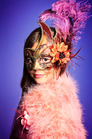 Beautiful little girl in festive dress and mask posing at studio. Stock Photo - 16711688