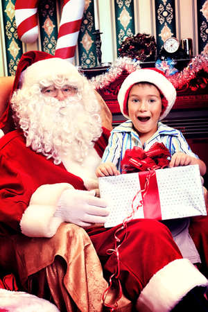 Santa Claus giving a present to a little cute boy at home. Stock Photo - 16711701