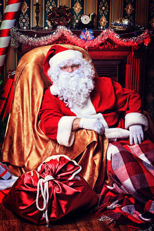 Santa Claus having a rest in a comfortable chair near the fireplace at home. Stock Photo - 16711687