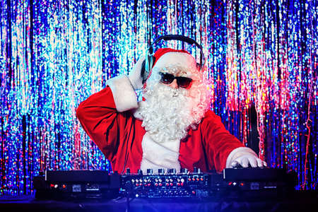 DJ Santa Claus mixing up some Christmas cheer. Disco lights in the background. Stock Photo - 16711706