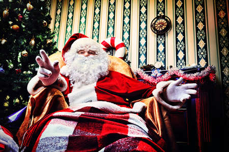 Santa Claus having a rest in a comfortable chair near the fireplace at home.  Stock Photo - 16711690