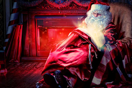 Santa Claus having a rest in a comfortable chair near the fireplace at home.  Stock Photo - 16740086