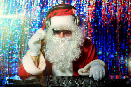 DJ Santa Claus mixing up some Christmas cheer. Disco lights in the background. Stock Photo - 16740082