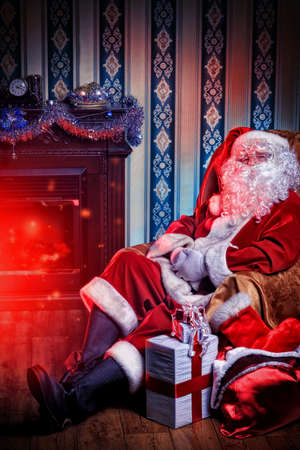 Santa Claus having a rest in a comfortable chair near the fireplace at home. Stock Photo - 16740079