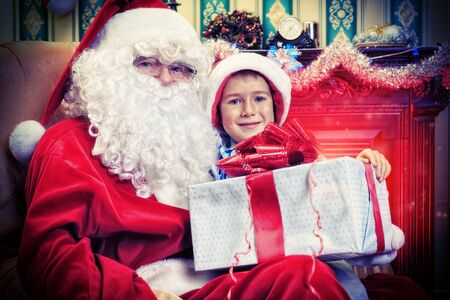 Santa Claus giving a present to a little cute boy at home. photo