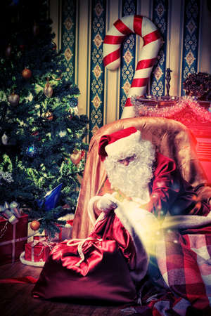 Santa Claus having a rest in a comfortable chair near the fireplace at home. Stock Photo - 16740083