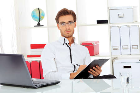 Handsome businessman is working on a laptop at the office. Stock Photo - 16890630