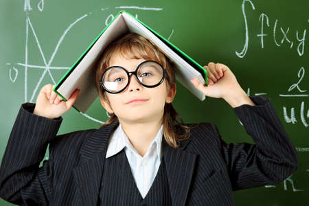 Portrait of a schoolboy in big round spectacles with a book at a classroom. Stock Photo - 16763818
