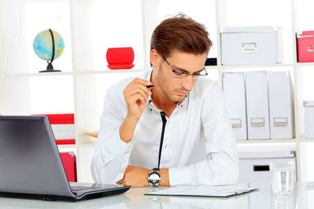Handsome businessman is working on a laptop at the office. Stock Photo - 16763812
