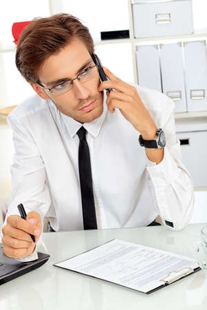 Handsome businessman is calling on his cell phone at the office. Stock Photo - 16763810