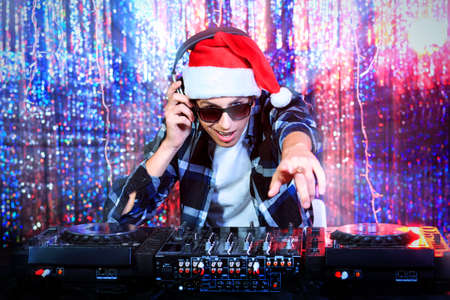 new years eve party: DJ man mixing up some Christmas cheer. Disco lights in the background.