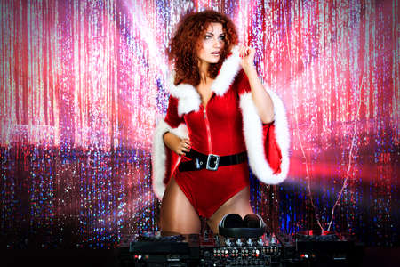 disc jockey: Attractive DJ girl mixing up some Christmas cheer. Disco lights in the background.