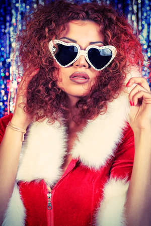 Attractive young woman in Christmas clothes on a party. Disco lights in the background. Stock Photo - 16763837