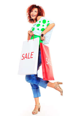 Happy young woman standing with shopping bags. Isolated over white. Stock Photo - 16763804