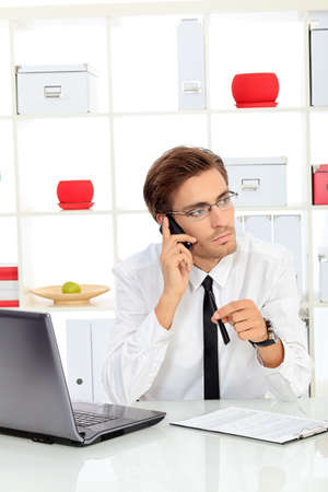 Handsome businessman is calling on his cell phone at the office. photo