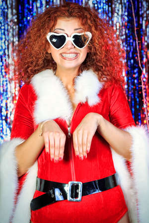 Attractive young woman in Christmas clothes on a party. Disco lights in the background. Stock Photo - 16763816