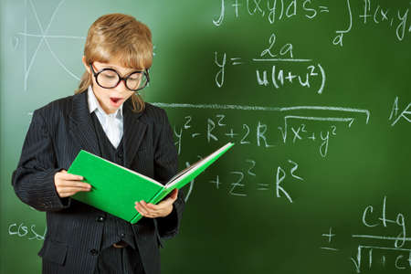 Portrait of a schoolboy in big round spectacles with a book at a classroom. Stock Photo - 16763828