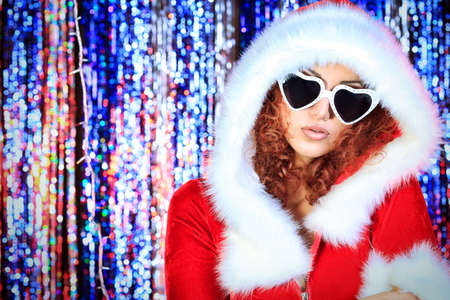 Attractive young woman in Christmas clothes on a party. Disco lights in the background. Stock Photo - 16763836